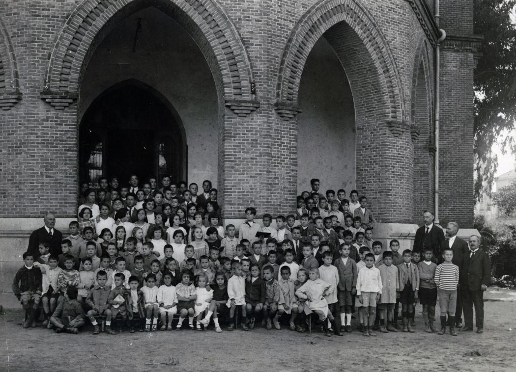 Alumnos y alumnas en el pórtico del colegio El Porvenir con sus profesores (ca. 1919).